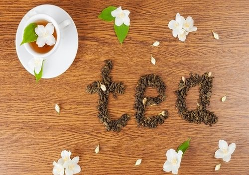 "the word ""tea"" from leaves of green tea on a wooden surface near jasmine flowers and a white cup of tea"